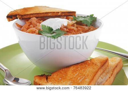 image of vegetable soup with spoon and sour cream