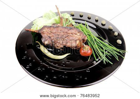 served main dish : lamb meat ribs on plate with hot peppers and capers on black plate isolated over white background