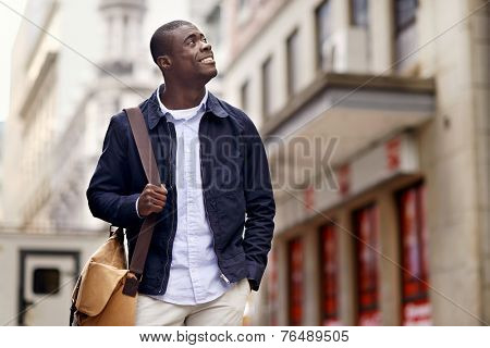 Friendly young trendy african black man walking around the urban city having fun
