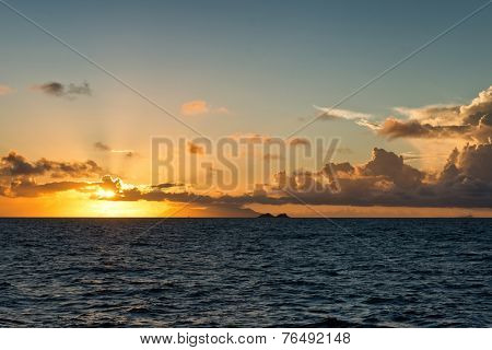 Colorful orange tropical ocean sunset lighting up the horizon and sky over a calm blue sea with scattered cloud