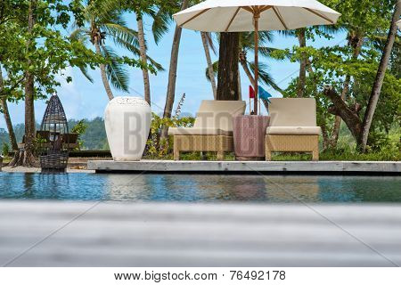 Elegant Beach Chairs and Umbrella at Swimming Pool Side. A perfect Venue for Relaxation.