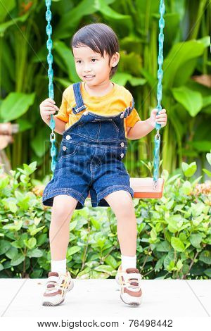 asian boy playing swing