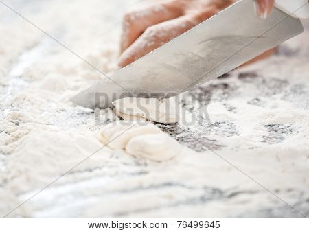 Cropped image of chef's hand cutting dough at messy counter in commercial kitchen