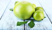 foto of sweetie  - Ripe sweetie and limes on wooden background - JPG