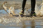 image of big-foot  - The feet of a child splashing in a big muddy puddle - JPG