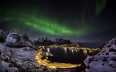 picture of reining  - A man looking at the northern lights over Reine Lofoten islands Norway - JPG