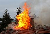 picture of firefighter  - Burning house roof - JPG