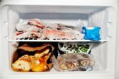 stock photo of frozen  - Freezer compartment of a refrigerator containing meat and frozen vegetables as well as bread