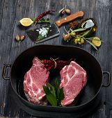 stock photo of cauldron  - Fresh cuts of meat in a cauldron and spice olive oil on old wooden background - JPG