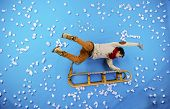 image of toboggan  - Happy young man on sled having fun against the blue background with snowflakes - JPG