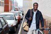 pic of commutator  - young trendy black african hipster man with bicycle walking in urban city on way commute to work - JPG