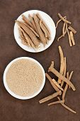 stock photo of ginseng  - Ginseng ashwagandha herb root and powder over handmade lokta paper background - JPG