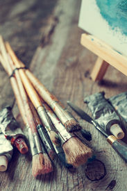 picture of tubes  - Artistic paintbrushes tubes of oil paint palette knife and easel with oil painting on old wooden desk - JPG