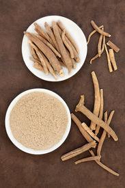 picture of ginseng  - Ginseng ashwagandha herb root and powder over handmade lokta paper background - JPG