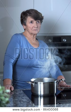 Worried Grandma Standing In The Kitchen