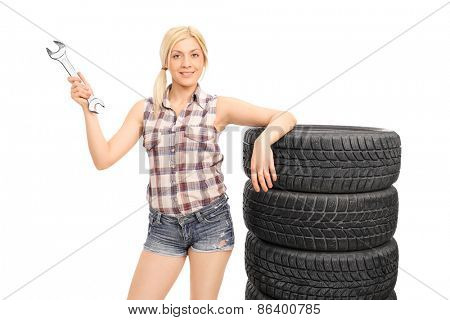 Attractive female mechanic holding a huge wrench and standing next to a stack of tires isolated on white background