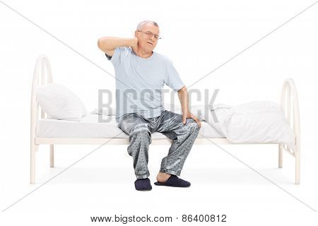 Senior in pajamas feeling pain in the neck seated on a bed isolated on white background