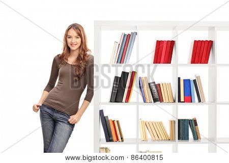 Casual young woman leaning on a white wooden bookshelf and looking at the camera isolated on white background