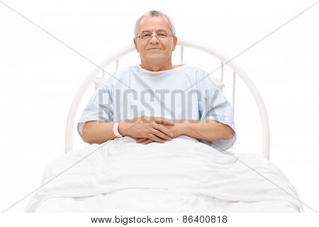 Cheerful mature patient lying in a hospital bed and looking at the camera isolated on white background