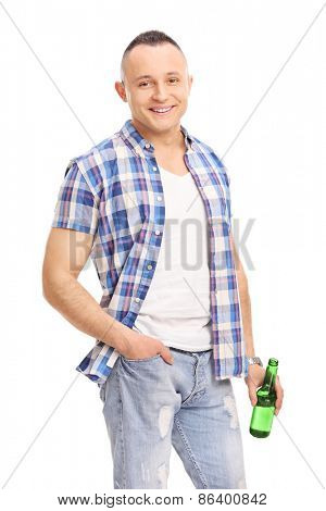 Vertical shot of a casual young guy holding a bottle of beer and posing isolated on white background