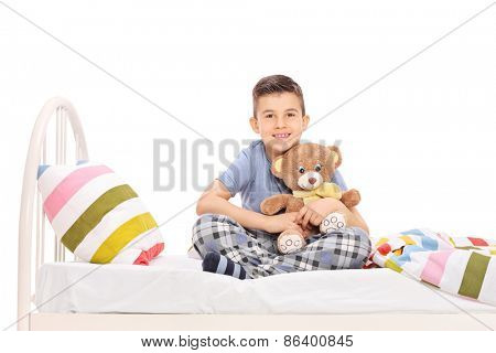 Studio shot of a happy little boy in pajamas, sitting in bed and hugging a teddy bear isolated on white background