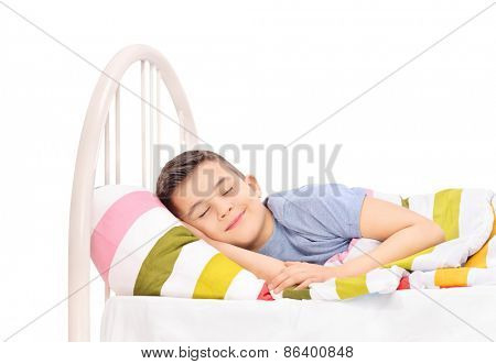 Cheerful little boy sleeping in a comfortable bed and dreaming sweet dreams covered with a blanket isolated on white background
