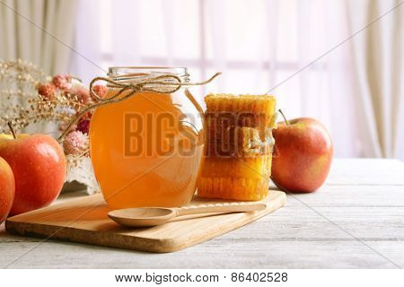 Delicious honey with apple on table on light background