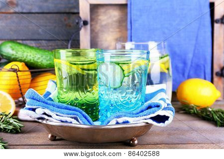 Fresh water with lemon and cucumber in glassware with napkin on wooden background