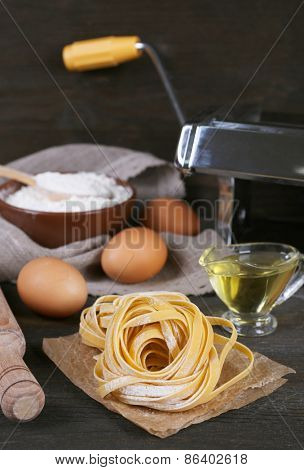 Preparing pasta by pasta machine on rustic wooden background
