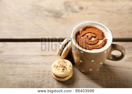 Cup of coffee  and macaroons on old wooden table