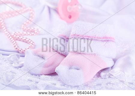 Pink baby socks on cloth close-up
