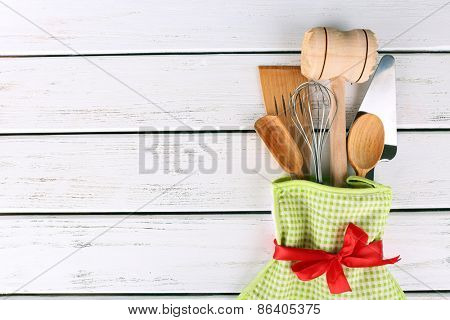 Set of kitchen utensils in mitten on wooden background