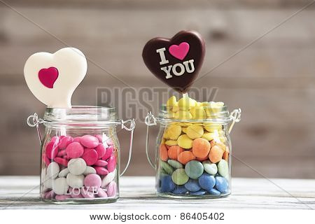 Sweet candies in glass jar with hearts on wooden background