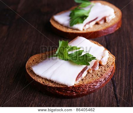 Sandwiches with lard and parsley on wooden background