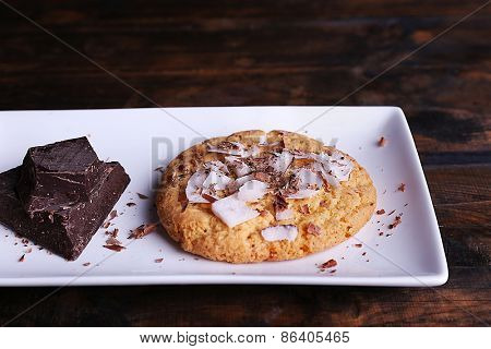 Cookie with chocolate and coconut chips on white plate and rustic wooden table background
