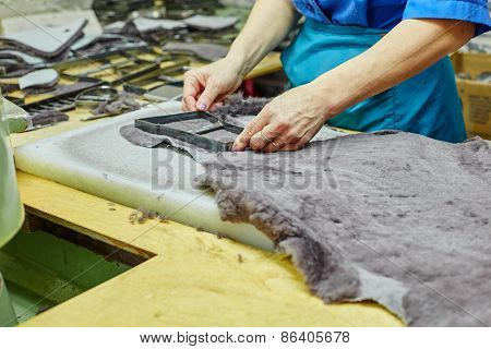 Production of fur insoles. Worker uses template