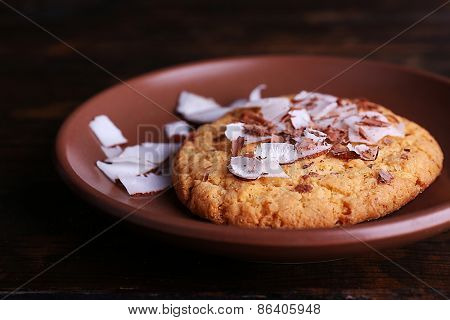 Cookie with coconut chips on plate and rustic wooden table background
