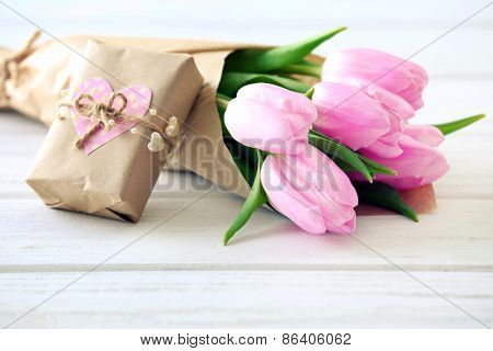 Beautiful pink tulips in paper with present box on wooden background