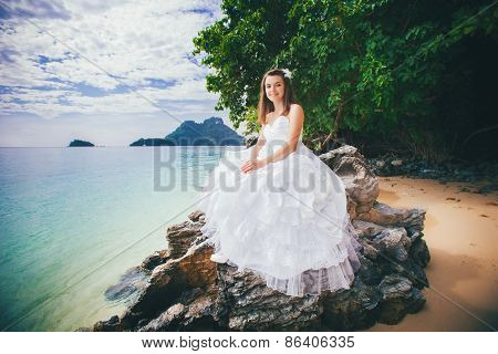 Young Bride Sits On Rock Against Azure Sea