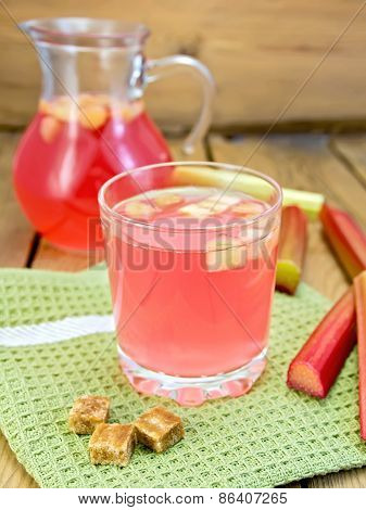 Compote from rhubarb in glassful and jug with sugar on board