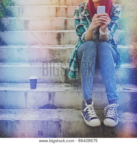 Hipster teenage girl with smart phone and takeaway coffee