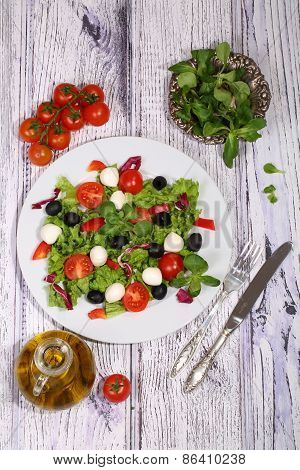 Salad With Tomatoes, Mozzarella, Olives, Cabbage And Ruccola