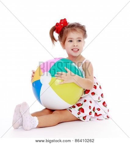 Girl in summer dress sitting on the floor with an inflatable bal