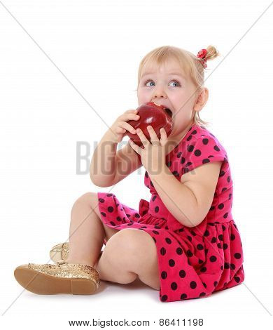 Little girl in red dress eating an apple sitting on the floor.