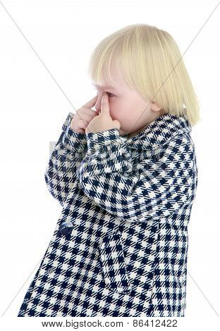 Caucasian little girl wipes her tears fingers.