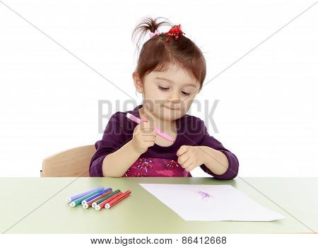 The little girl draws markers at the table