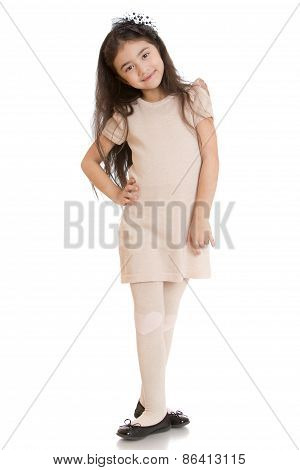 Dark haired girl posing in dress beige