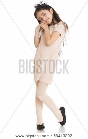 The dark-haired girl posing while standing in a beige dress