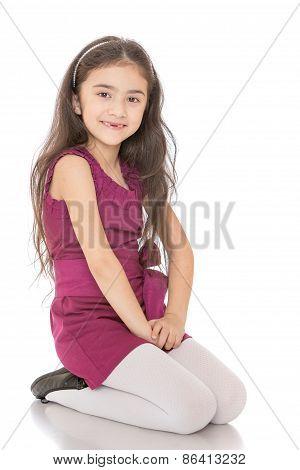Joyful dark-haired girl in purple dress sitting on her knees