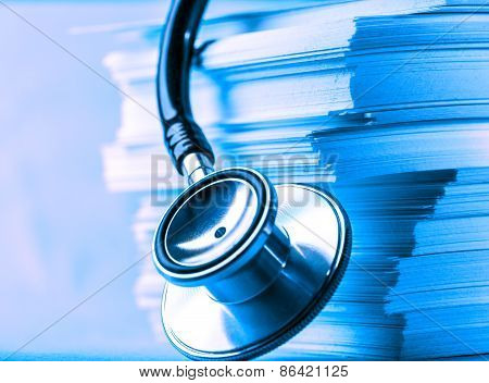 Stethoscope And Heap Of Paper Cards